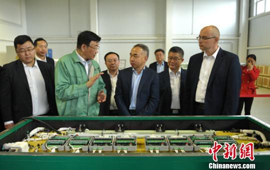 华黎向嘉宾们介绍超级电容生产情况。 刘忠俊 摄