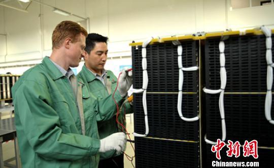 车间生产线上技术人员正在测试组装好的电容模块。 刘忠俊 摄