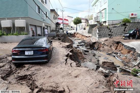 当地时间2018年9月6日,日本北海道地区发生强震,厚真町出现大规模塌方,多人被困。图为地震导致地面出现塌陷吞噬车辆。